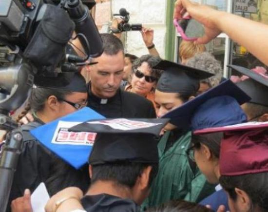 Father Sean Carroll prays with DREAMers